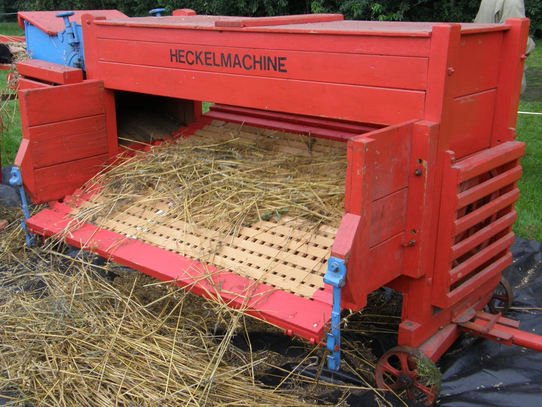 Ambachtelijke graanverwerking: machinaal dorsen van koren met een heckelmachine bij Onstwedder Gaarv'n.